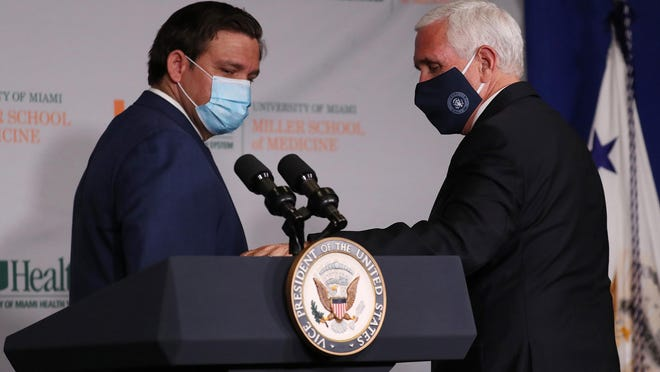 Vice President Mike Pence, right, and Florida Gov. Ron DeSantis leave after participating in a press conference at the the University of Miami Miller School of Medicine on July 27, 2020 in Miami. The Vice President participated in a roundtable with university leadership and researchers on the progress of a coronavirus vaccine.