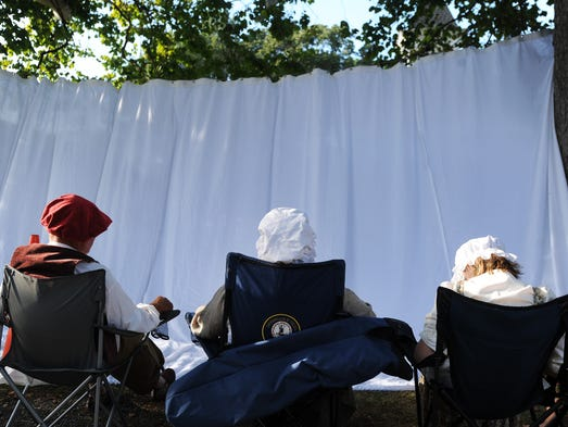 Actors sit behind the curtain as they wait for their