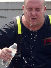 Bremerton firefighter/paramedic Brian Allen douses himself with a bottle of water after working on the two-alarm fire at the corner of Callow and 11th in Bremerton on Thursday, August 3, 2017.