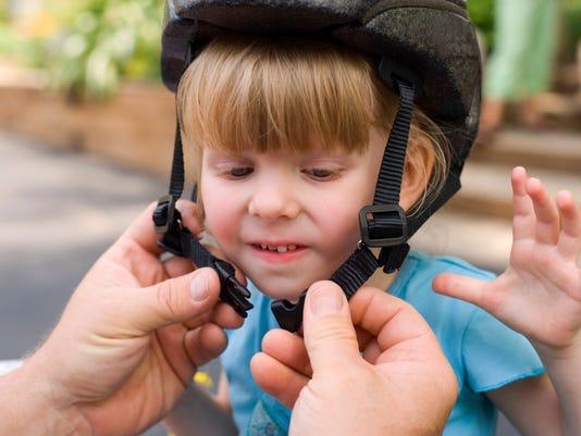 Person helping girl fasten safety helmet