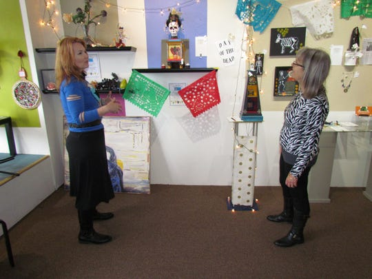 """Silverton artist Lori Lee McLaughlin and local immigration legal aid attorney Susana Ghio examine some of the """"Dia de los Muertos"""" art exhibits at White Oak Gallery. The exhibits are part of silent auction fundraiser for Somos Hispanas Unidas Silverton."""