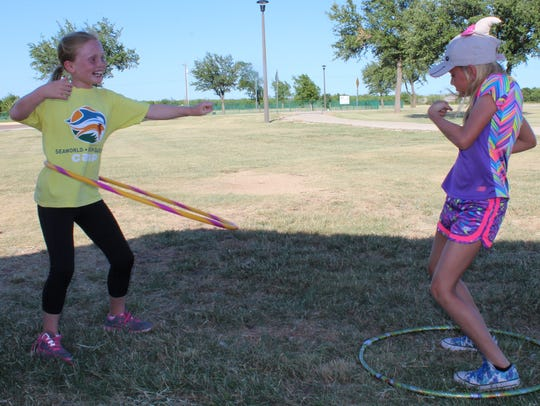 Girl Scouts Kamryn (left) and McKenna compare hula