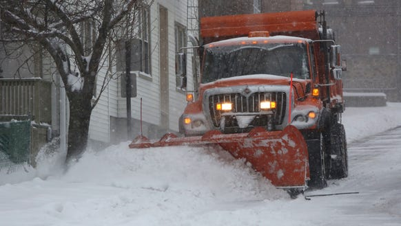 A plow clears the road during a steady snowfall, March