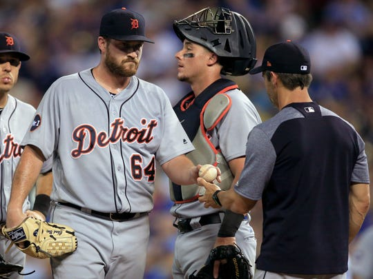 Tigers pitcher Chad Bell (64) hands the ball to manager Brad Ausmus during the sixth inning of the Tigers' 16-4 loss to the Royals on Thursday, July 20, 2017, in Kansas City, Mo.