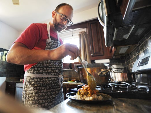 Chef Joel Neirynck-Coon spoons curry lime chicken over