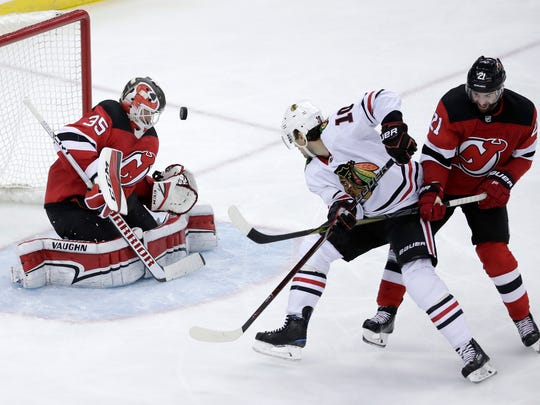 New Jersey Devils goalie Cory Schneider, left, blocks a shot as teammate right wing Kyle Palmieri, right, defends against Chicago Blackhawks left wing Patrick Sharp during the third period of an NHL hockey game, Saturday, Dec. 23, 2017, in Newark, N.J. (AP Photo/Julio Cortez)
