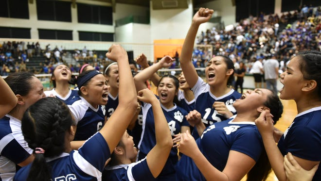 The Academy of Our Lady of Guam Cougars celebrate moments after winning the 2016 Independent Interscholastic Athletic Association of Guam Girls Volleyball League Championship game against the George Washington Geckos in four sets, at the University of Guam Calvo Field House on Oct. 21.