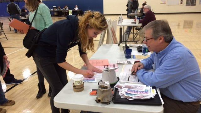 Rick Schmidt, Nekoosa's director of public works, helps student Samantha Smith pay her utility bills during a financial literacy simulation at Nekoosa High School.