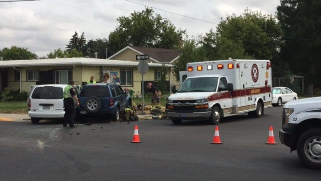 Emergency responders work to remove two vehicles involved in a crash on 15th Street North on Wednesday. Two people were taken to the hospital, including a bicyclist struck by the vehicles