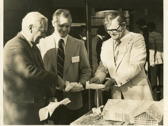 This photo, donated by Herb Savage to the MIHS shows Savage, right, slicing cake with Frank Mackle, Jr., left, and Frank Mackle III.