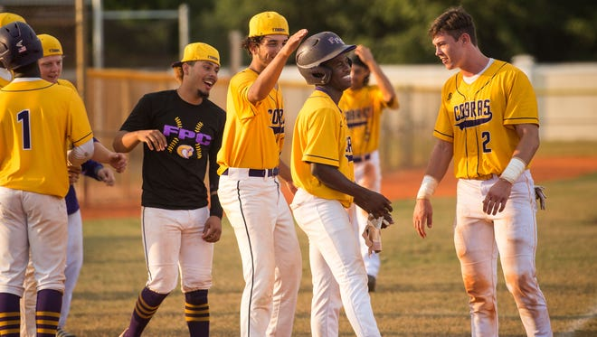 Fort Pierce Central's Tyreik Martin (right of center) is congratulated by teammate Dan Vaughn (right), as closing pitcher Darwin Morales pats his helmet, after stealing home on an errant pitch to score the game-winning run against John Carroll Catholic during the high school baseball game Monday, April 9, 2018, at Fort Pierce Central High School.