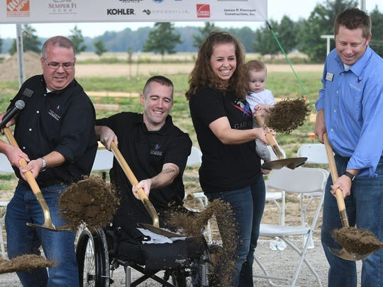 US Army Captain Nick Vogt, retired, along with his wife, Lauren, and son, Nathan, break ground on their new home with members and partners of the Gary Sinise Foundation on Tuesday morning.
