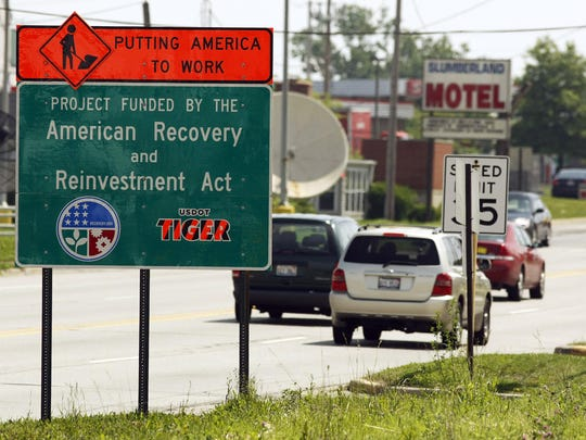 """FILE - In this June 18, 2009, file photo a road sign reading """"Putting America to Work"""" and """"Project Funded by the American Recovery and Reinvestment Act"""" is seen along Route 120 in Waukegan, Ill. President Donald Trump disparaged his predecessor's economic stimulus spending Tuesday as a windfall for social programs and said he's unaware of anything built from the money steered to infrastructure. (AP Photo/Jim Prisching, File)"""