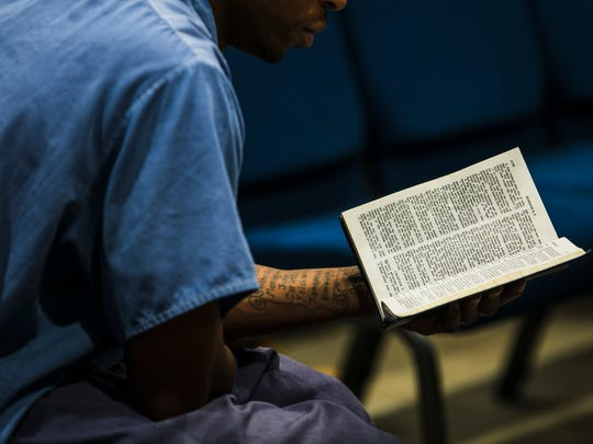 An inmate reads a passage from the Book of Romans in the Bible as Pastor Bob Duckens delivers a message to prisoners at London Correctional Institution in London, Ohio.