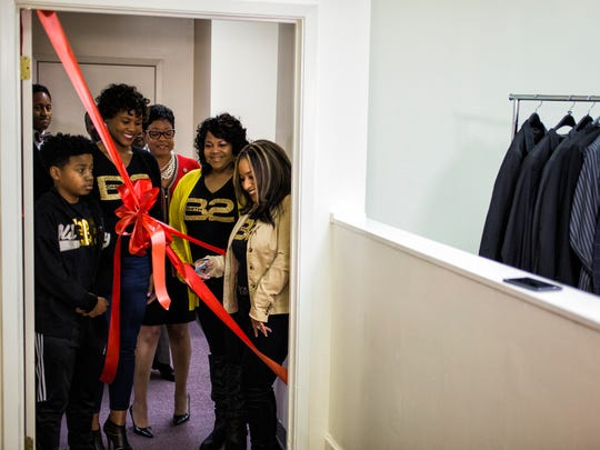 Braylon Smith, left, looks at his mother, Towanda Peete-Smith, as she readies to cut the ribbon during the grand opening of the Bernal E. Smith II Empowerment Center at 413 N. Cleveland, inside the Memphis Urban League, on Feb. 28, 2018.