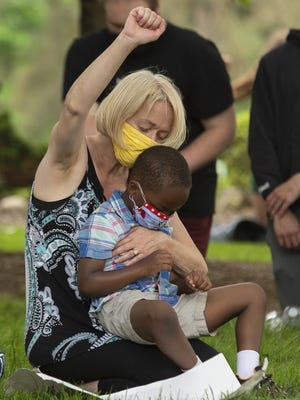 Demonstrators, including Virginia Comi and her son, Charlie Comi, 5, kneel for 8 minutes and 46 seconds at Silver Lake Police Department in memory of George Floyd Wednesday afternoon.