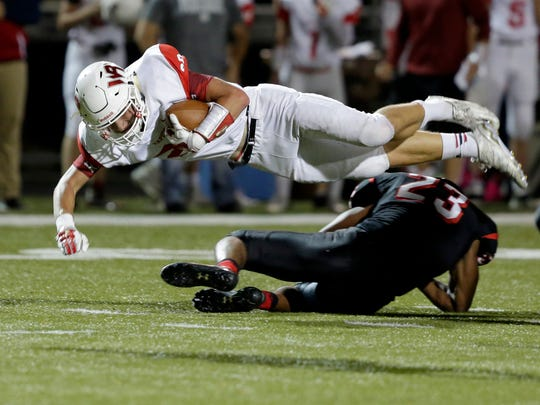 Wisconsin Rapids' Isaac Pelot leaps horizontally over SPASH's Keon'te Williams during the game between Stevens Point and Wisconsin Rapids at the rivalry Ol' River Jug game, Sept. 23, 2016.