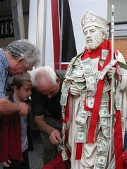 St. Bartholomew/UNICO Italian Festival returns Sept. 1 to 4 to St. Bartholomew's Church in Scotch Plains. Pictured are patrons sticking money to an a statue for good fortune.