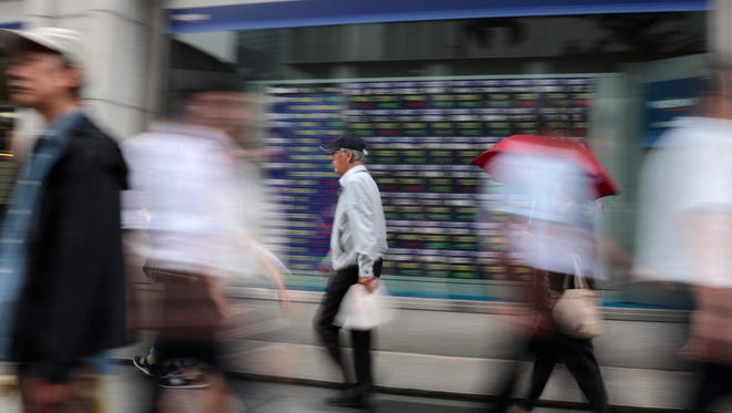 People walk past an electronic stock indicator of a securities firm in Tokyo, Monday, Aug. 14, 2017.