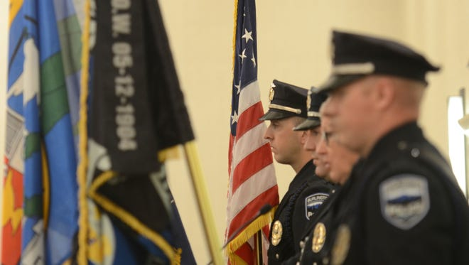 Burlington police Cpl. Kevin Wilson holds the Stars and Stripes as part of the honor guard during the recitation of the Pledge of Allegiance at the annual Queen City Police Foundation awards luncheon on Monday, March 13, 2017, at the Hilton Hotel in Burlington.