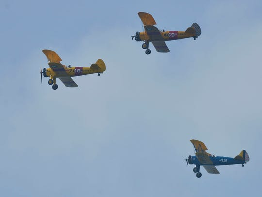 The crowd assembled on Pensacola Beach gets and early view of the upcoming beach airshow with this fly over of three Stearman biplanes Friday morning.
