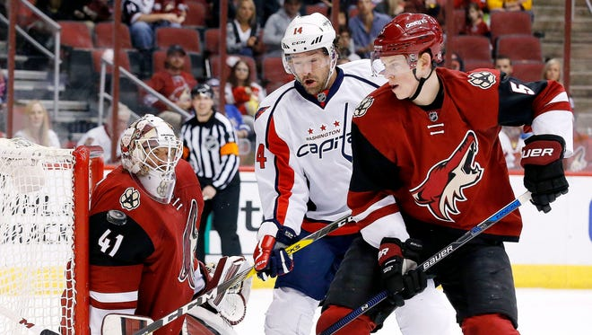 Arizona Coyotes' Mike Smith (41) makes a save off his shoulder as Coyotes' Connor Murphy (5) and Washington Capitals' Justin Williams (14) work for position during the first period of an NHL hockey game Saturday, April 2, 2016, in Glendale, Ariz.