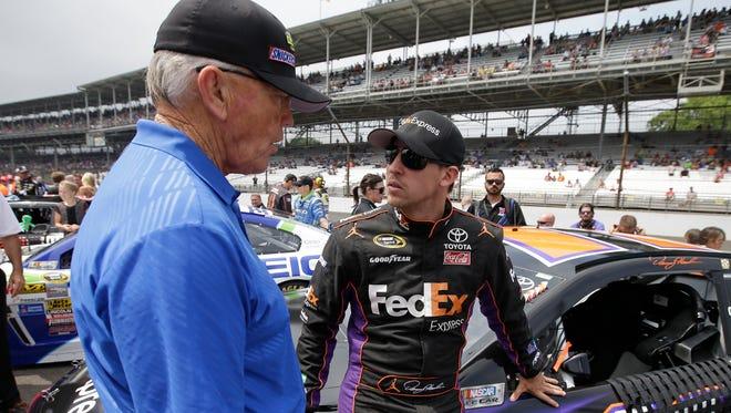 NASCAR team owner Joe Gibbs, left, talks with Denny Hamlin before the Brickyard 400.
