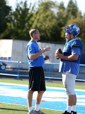 McNary Assistant Coach Scott Gragg, a former Silverton player and coach who played 11 seasons in the NFL, talks with his son, Brian, during practice on Wednesday, Sept. 21, 2016, in Keizer.