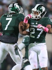 Michigan State's Demetrious Cox (7) and Kahri Willis (27) celebrate after stopping Indiana in the second half on Saturday, Oct. 24, 2015, at Spartan Stadium in East Lansing, Mich.