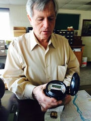Interim Public Works and Utilities Director Joe Gehin holds a Neptune water meter at Wausau Water Works on Thursday, March 12, 2015.