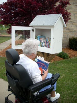 A patron visits a Little Free Library. A new Little Free Library is now operating in Cotter.