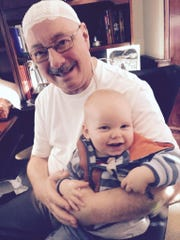 Pictured are Dr. Robert Saylor with his grandson, Triton.