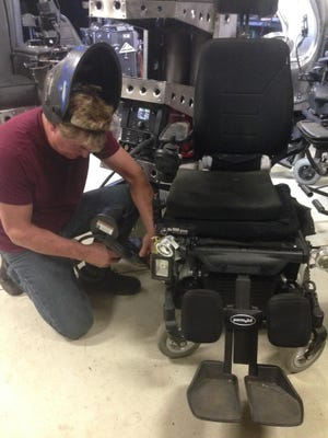 Lance working on one of the wheelchairs.