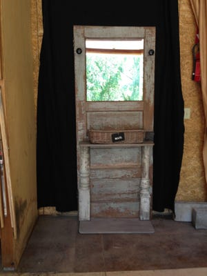 This hall tree is made from an old door, antique porcelain handles, porch posts and an aging table.