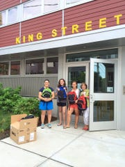 Backpacks are received at the King Street Center by Nina Knorr, second from right, after- school program staff member and Executive Director Vicky Smith, right.