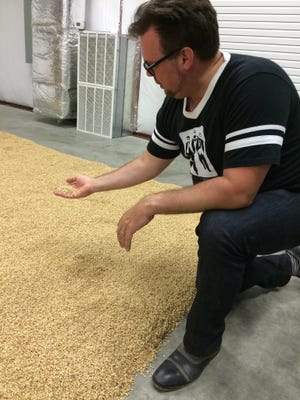 Corsair founder Darek Bell inspects the sprouted barley as it dries on the floor of his new malt house.