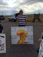 Laura Greenwood of Brady, TX, holds a sign that says her Alamogordo-born husband and 11 of his relatives died of cancers she blames on the Trinity nuclear bomb test.