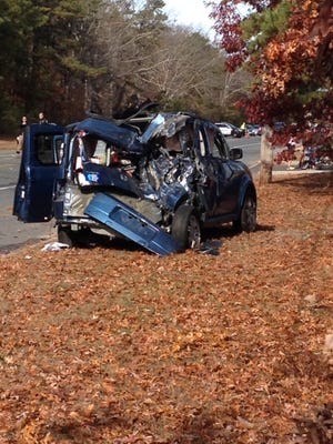 A car is crumpled along Route 72, where police say it collided with a dump truck full of stone.