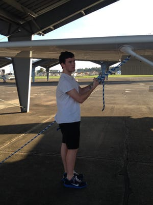 Logan Stephens, 17, one of the youngest pilots in the state, prepares the plane at Bobby Chain regional airport before taking off.
