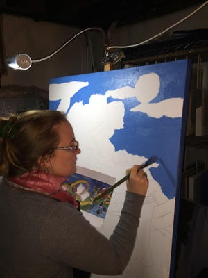 """Isabel Speronza works on """"Tablet to Tablet,"""" the triptych she and her husband, Joseph, are painting on for the Roxbury Public Library."""