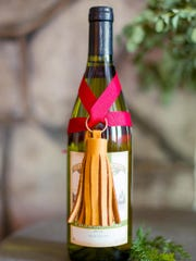 A leather tassel adorns a bottle of wine. Often inexpensive to buy, tassels also can be made from thread, yarn, even paper for decoration on holiday gifts.