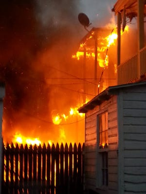 Flames engulf the rear of a home in the 700 block of West Princess Street Monday morning.