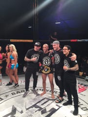 Jordan Leavitt poses with his team, and the title belt
