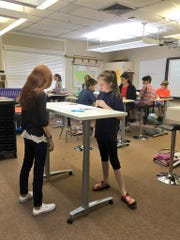 Sixth-graders in Lee Sanders' social studies class at Alexandria Country Day School have the option to sit or stand at new tables donated by Baker Manufacturing.