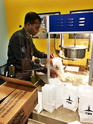 Enoch Paul, Customer Service & Safety Supervisor at Fort Wayne International Airport, makes popcorn for a tenant appreciation day.