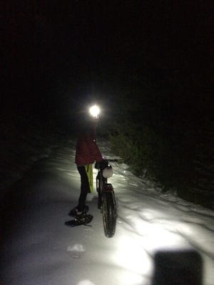 Endurance rider Blake Bockius wearing showshoes as he pushes his fat bike during a wintertime crossing of the Sierra Nevada crest.