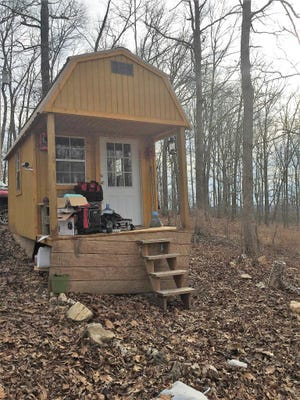 Photograph shows Jonathon and Charles Mooneyham's tiny cabin in Missouri.