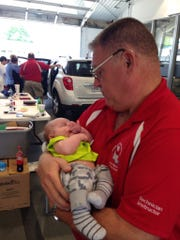 Sgt. Kevin Allen holds 8-week-old Wyatt Colt Brown on Saturday as child safety seat inspectors make sure the boy's safety seat is installed correctly in his mother's truck.