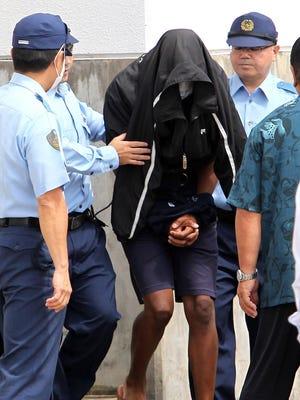 Former U.S. Marine Kenneth Franklin Shinzato is escorted by police officers from Uruma Police Station in Uruma, Okinawa, Japan, on May 20, 2016.
