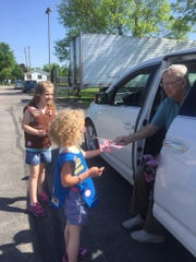 Bob Schneider gives out a flag to a child before the Memorial Day parade in Kewaunee.
